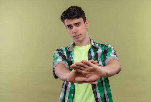 Kaukaski młody człowiek ubrany w zieloną koszulę pokazując gest nie na odizolowanej zielonej ścianie