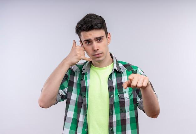 Kaukaski młody człowiek ubrany w zieloną koszulę pokazując gest połączenia i gest na na białym tle białej ścianie
