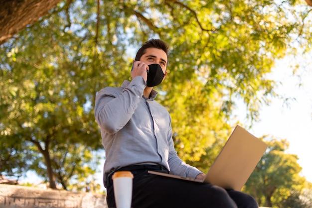 Kaukaski młody człowiek w masce na twarzy pracuje i studiuje inżynierię, rozmawia przez telefon i używa swojego laptopa w pięknym parku w słoneczny dzień.