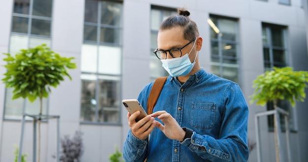 Kaukaski młody człowiek w okularach i masce medycznej, dotykając i przewijając telefon komórkowy na ulicy miasta. przystojny mężczyzna w okularach sms-y wiadomości na smartfonie na zewnątrz. gadżet za pomocą koncepcji.