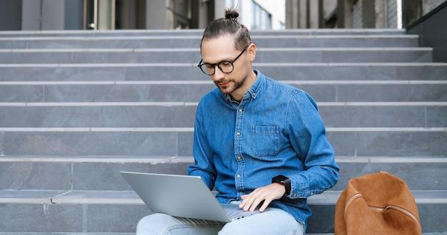Kaukaski młody człowiek w okularach siedzi na schodach na zewnątrz i rozmawia przez kamerę internetową na komputerze przenośnym. mężczyzna student lub freelancer czatuje na ulicy i myśli. wideo rozmowa. oddając kciuk w górę.