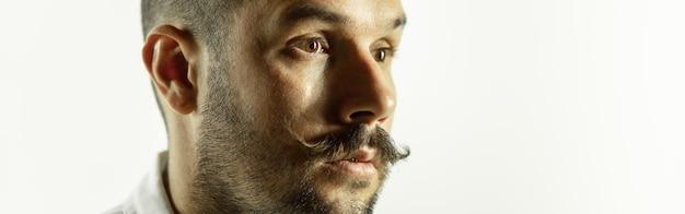Kaukaski młody człowiek z bliska strzał na tle studio, ulotka. pojęcie ludzkich emocji, wyraz twarzy, sprzedaż, reklama. copyspace. piękny męski model z jasnymi, wyrazistymi emocjami.
