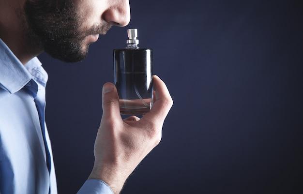 Kaukaski młody człowiek zapachu perfum.