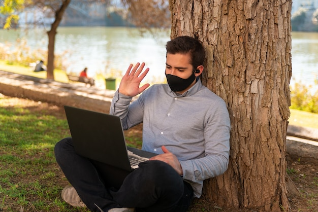 Kaukaski młody mężczyzna siedzi na trawie, a wita się na spotkaniu online na laptopie przy użyciu swojego laptopa w pięknym parku w słoneczny dzień.