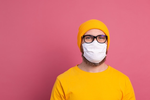 Kaukaski młody mężczyzna w okularach z jednorazową maską medyczną zapobiegającą infekcjom, chorobom układu oddechowego, takim jak grypa