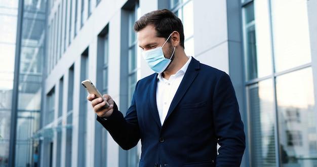 Kaukaski młody przystojny mężczyzna w masce medycznej, dotykając i przewijając telefon komórkowy na zewnątrz w centrum biznesowym. szczęśliwy biznesmen w ochrony dróg oddechowych gaszenie wiadomości na smartfonie. pandemia.