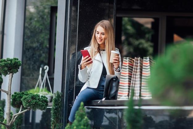 Kaukaski moda kobieta z filiżanką kawy siedzi w pobliżu witryn sklepowych na ulicy na zewnątrz, aby odpocząć podczas przerwy na kawę.
