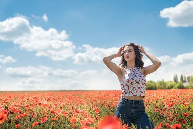 Kaukaski modelka cieszy się życiem na polu maku w słoneczny dzień. zdrowy styl życia