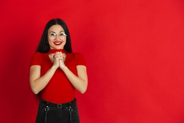 Kaukaski monochromatyczny portret młodej kobiety na czerwonej ścianie emocjonalnej i ekspresyjnej