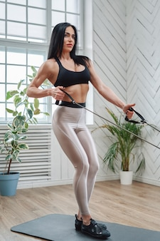 Kaukaski muskularny i średnim wieku kobieta w sportowej pozach na macie pobyt i ćwiczenie z gumkami w pokoju.