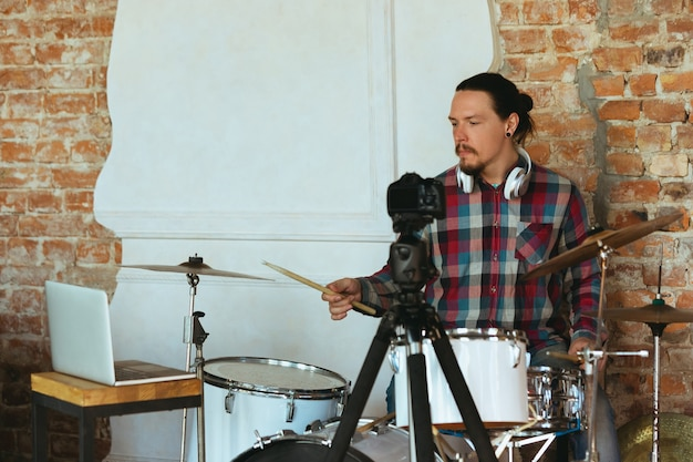 Kaukaski muzyk grający na perkusji podczas koncertu online w domu, odizolowany i poddany kwarantannie.