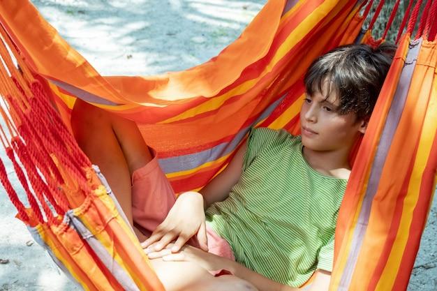 Kaukaski nastolatek chłopiec relaksuje się w jasnym pomarańczowym hamaku w paski letni aktywny wypoczynek dla dzieci c