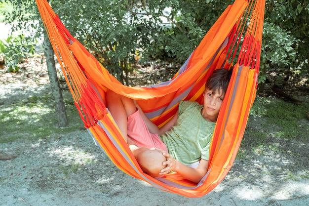 Kaukaski nastolatek chłopiec relaksuje się w jasnym pomarańczowym hamaku w paski letni aktywny wypoczynek dla dzieci