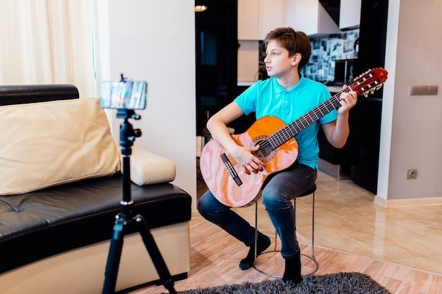 Kaukaski nastolatek gra na gitarze, mając lekcje gry na gitarze online, ciesząc się ulubionym