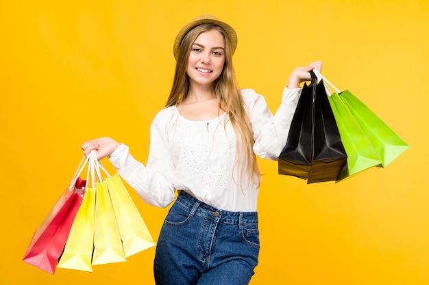 Kaukaski nastolatka na żółtym tle. stylowa młoda kobieta z torby na zakupy w rękach - obraz