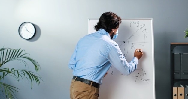 Kaukaski nauczyciel mężczyzna w masce medycznej i okularach stoi przy tablicy w klasie i mówi klasie prawa fizyki lub geometrii. koncepcja pandemii. szkoła podczas koronawirusa. wykład wychowawczy.