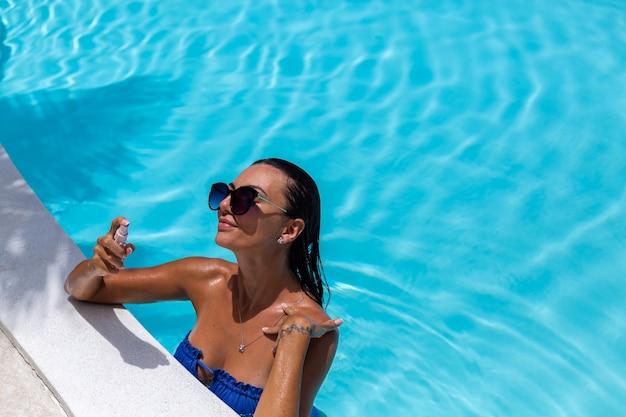 Kaukaski opalona kobieta błyszcząca brązowa skóra przy basenie w niebieskim bikini w słoneczny dzień
