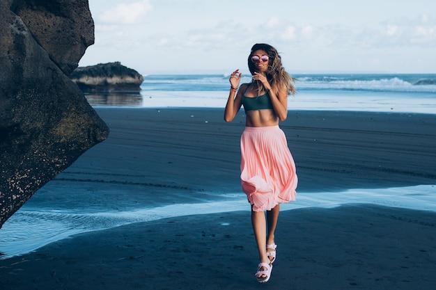 Kaukaski, opalona kobieta w malutkiej bluzce i różowej spódniczce na czarnej, piaszczystej plaży