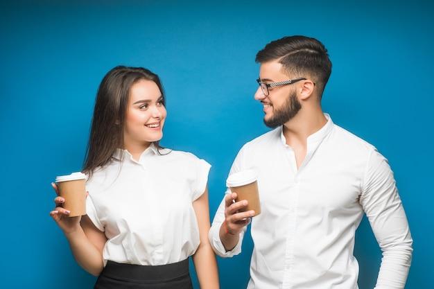Kaukaski para biznesu stojąc razem na niebiesko podczas przerwy na kawę.