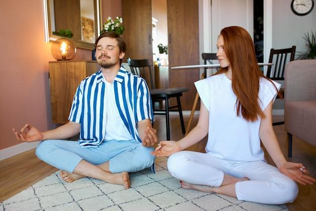 Kaukaski para praktykuje jogę w domu w pozycji lotosu