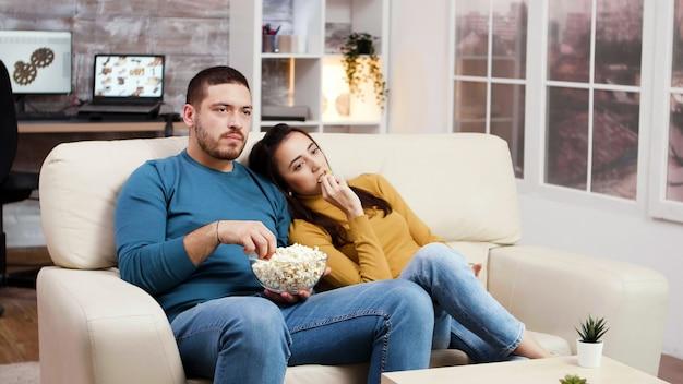 Kaukaski para relaks przed telewizorem w salonie jedzenie popcornu z frytkami.