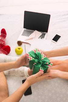 Kaukaski para z prezentem. laptop i telefon dla osób siedzących na podłodze przy kolorowych skarpetkach. boże narodzenie, miłość, koncepcja stylu życia
