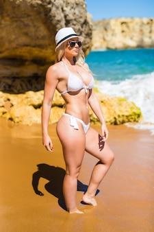 Kaukaski pasuje szczupła drobna kobieta w bikini i okularach przeciwsłonecznych na kamienistej plaży. motywacja do utraty wagi