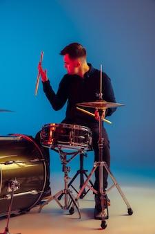 Kaukaski perkusista męski improwizujący na niebieskim tle studia w świetle neonowym