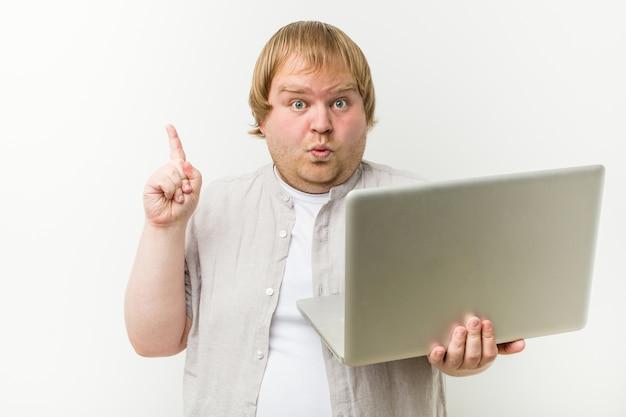 Kaukaski plus rozmiar mężczyzna trzyma laptopa mając jakiś świetny pomysł, pojęcie kreatywności.