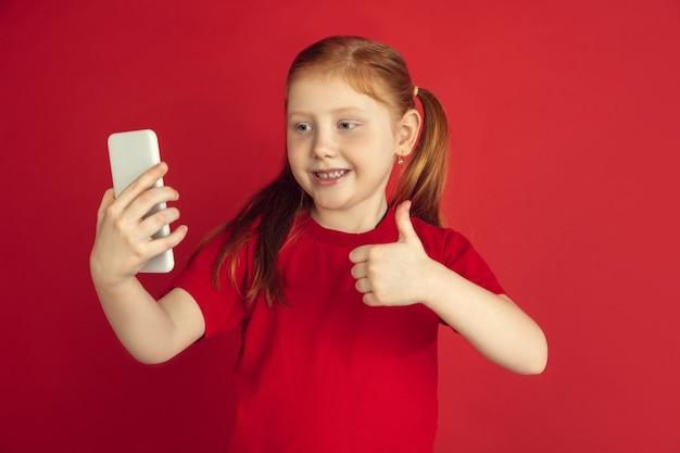 Kaukaski portret małej dziewczynki na białym tle na czerwonym studio