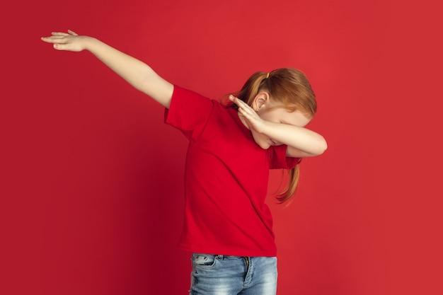 Kaukaski portret małej dziewczynki na białym tle na koncepcji emocji czerwonej ściany