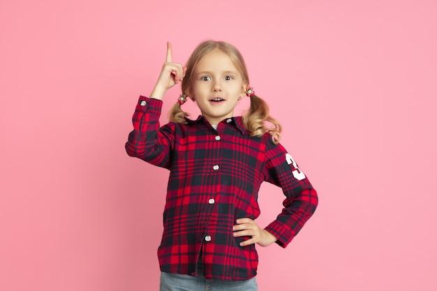 Kaukaski portret małej dziewczynki na różowej ścianie studia