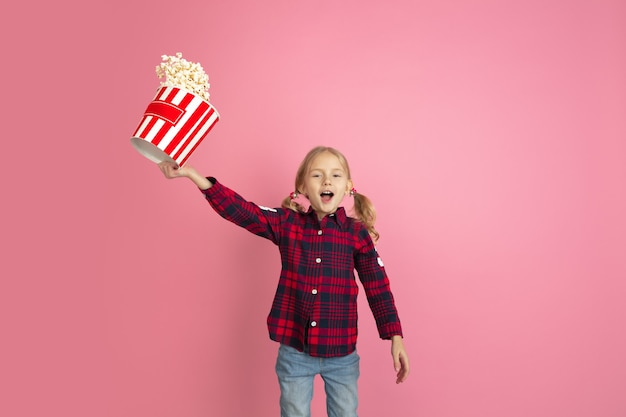 Kaukaski portret małych dziewczynek na koncepcji kina różowej ściany