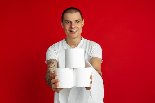 Kaukaski portret młodego mężczyzny na czerwonej ścianie - trzymając papiery toaletowe, niezbędne towary podczas kwarantanny i samoizolacji. pojęcie ludzkich emocji, sprzedaży, blokady koronawirusa, finansów.
