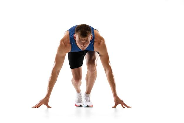 Kaukaski profesjonalny męski biegacz sportowiec trening na białym tle na białej ścianie dla ad