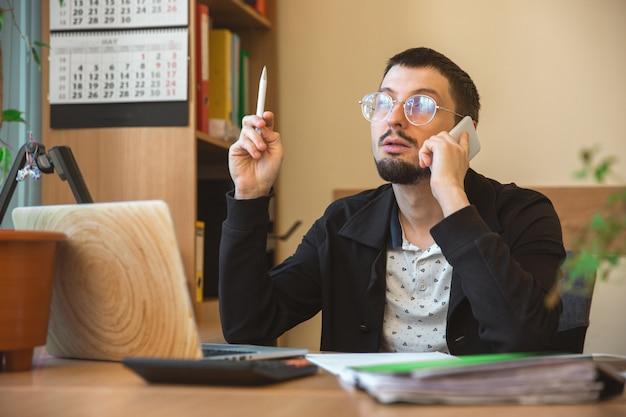 Kaukaski przedsiębiorca, biznesmen, kierownik pracujący skoncentrowany w biurze, odnoszący sukcesy