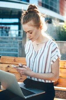 Kaukaski przedsiębiorca z rudymi włosami i piegami rozmawiający z kimś przy użyciu telefonu komórkowego, siedząc na ławce na zewnątrz z laptopem