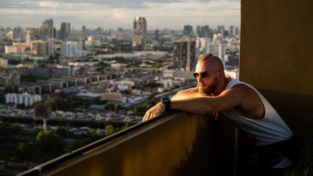 Kaukaski przystojny brodaty brutalny mężczyzna, podziwiając zachód słońca i widok na bangkok z wysokiego piętra