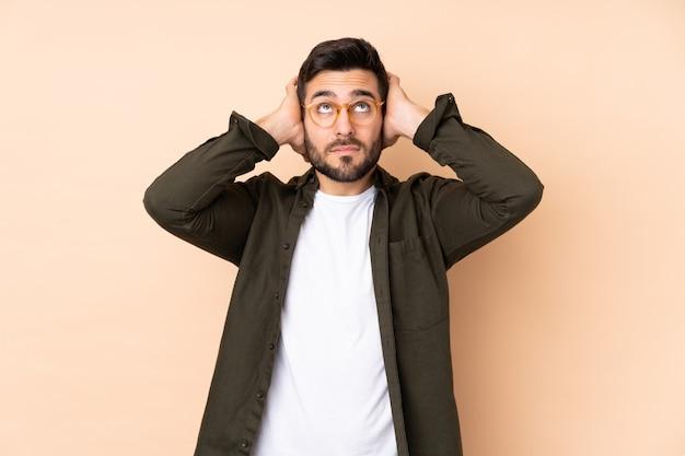 Kaukaski przystojny mężczyzna na białym tle na beżowej ścianie sfrustrowany i obejmujące uszy