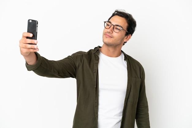 Kaukaski przystojny mężczyzna na białym tle robi selfie