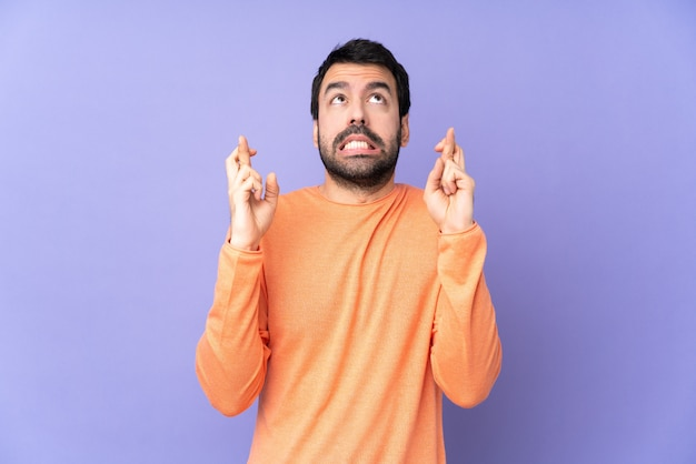 Kaukaski przystojny mężczyzna na fioletowe ściany z palcami skrzyżowanymi i życząc jak najlepiej