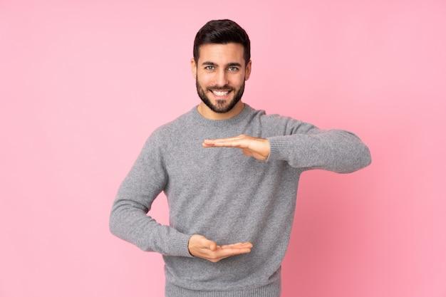 Kaukaski przystojny mężczyzna na izolowanych ścianach gospodarstwa copyspace wyimaginowanych na dłoni, aby wstawić reklamę