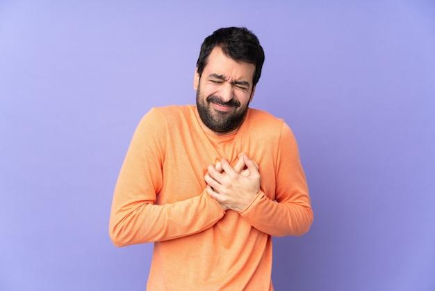 Kaukaski przystojny mężczyzna nad odosobnionymi purpurami ma ból w sercu