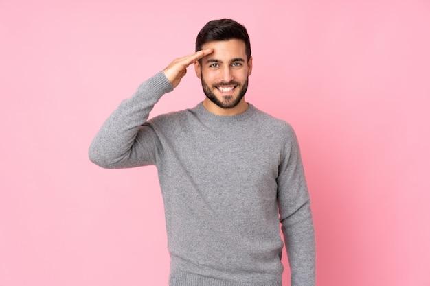 Kaukaski przystojny mężczyzna nad ścianą pozdrawiając ręką z happy wypowiedzi