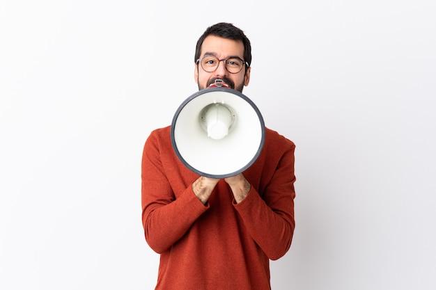 Kaukaski przystojny mężczyzna z brodą nad białym krzyczy przez megafon