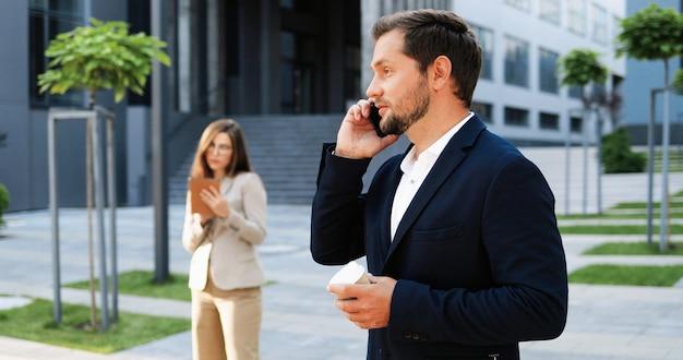 Kaukaski radosny młody stylowy mężczyzna rozmawia przez telefon i popijając gorący napój rano na ulicy. przystojny szczęśliwy mężczyzna mówiąc na telefon komórkowy i picia kawy. na zewnątrz.