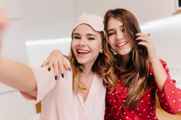 Kaukaski roześmiany dama robi selfie z przyjacielem w dobry weekendowy poranek. wyrafinowana dziewczyna z długimi fryzurami, bawiąca się z uroczą siostrą.