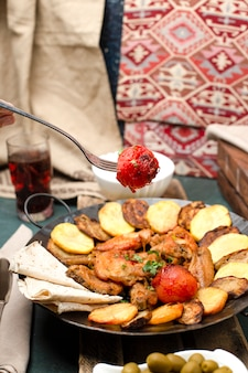 Kaukaski sac ichi z mięsem i ziemniakami podawany z chlebem lavash