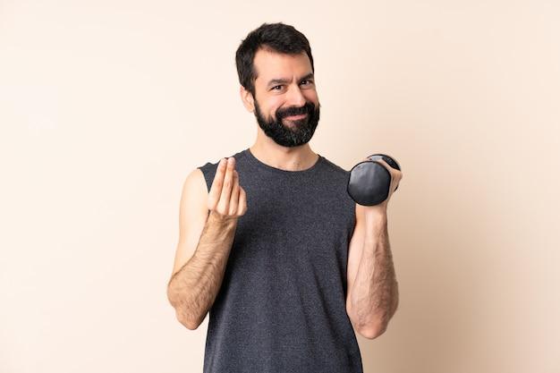 Kaukaski sport mężczyzna z brodą co podnoszenie ciężarów nad ścianą robi pieniądze gest