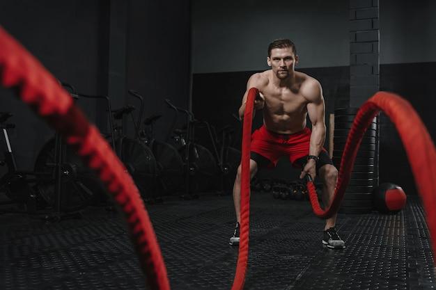 Kaukaski sportowiec wykonujący ćwiczenia na linach bojowych na siłowni crossfit